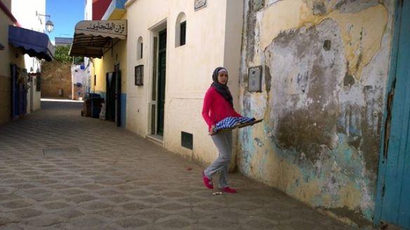 """Nas pequenas cidades do Marrocos ninguém compra o pão pronto. As pessoas preparam a massa em casa, e levam para assar em forno comunitários. Essa moça estava justamente levando o pão do forno para casa: e não ficou nada satisfeita de ser fotografada. Em tempo, dada a celeuma nos comentários do Facebook: só notei que a moça tinha ficado chateada depois de fotografá-la. Não fotografo agressivamente; não costumo fotografar quem, de cara, percebo que não quer ser clicado. Disse """"Pardon!"""" para a moça, ela me fez um aceno e seguimos em frente, cada uma na sua. Peço licença para fotografar quando é viável; não era o caso. Foto em movimento não rola assim. Página em movimento também não."""